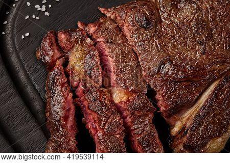 Closeup Of Sliced Juicy Beef Striploin Steak On Wooden Board