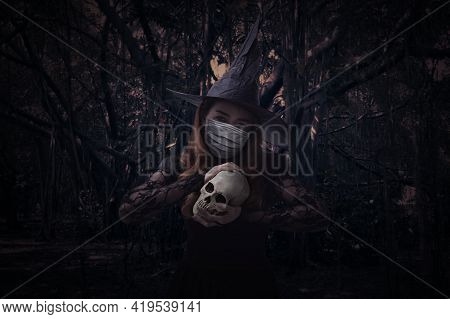 Halloween Witch Wearing Medical Face Mask Holding A Skull Standing Over Spooky Dark Forest With Tree