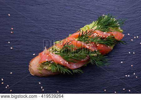 Appetizing Crispy Piece Of Baguette With Avocado And Smoked Salmon Fillet And Fresh Dill Sprigs And
