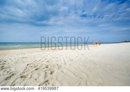 A Little Girl And Her Parents Walk On The Beach In Swimsuits On The Baltic Sea In Lithuania