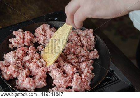 A Man Is Frying Minced Meat In A Pan. His Hand Stirs The Minced Pork And Beef With A Wooden Kitchen