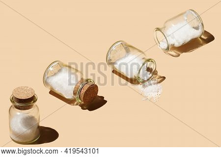Several Glass Jars With Cork Lids Containing Coarse Sea Salt And Sprinkled Salt On Pastel Yellow Sea