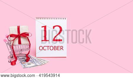 12th Day Of October. A Gift Box In A Shopping Trolley, Dollars And A Calendar With The Date Of 12 Oc