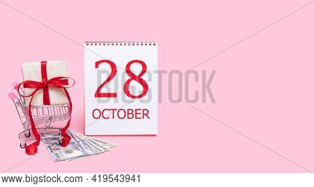 28th Day Of October. A Gift Box In A Shopping Trolley, Dollars And A Calendar With The Date Of 28 Oc