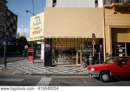 Cordoba, Argentina - January, 2020: Old Red Car Parked At The Corner Of The Street Near Empty Cafe N