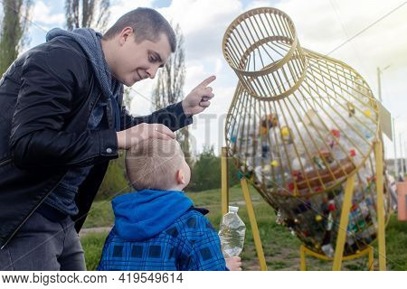 Dad And Son Throw The Plastic Bottle Into The Plastic Collection Container. Recycling And Disposal O