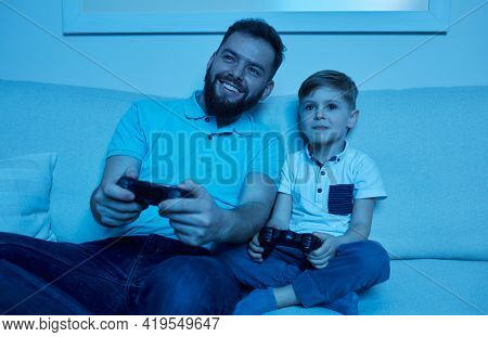 Content Bearded Man And Little Son Sitting On Sofa And Playing Videogame With Gamepads While Spendin