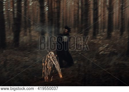 Blurry Silhouette Of An Evil Black Witch With A Skull In Her Hands Performing An Occult Satanic Ritu
