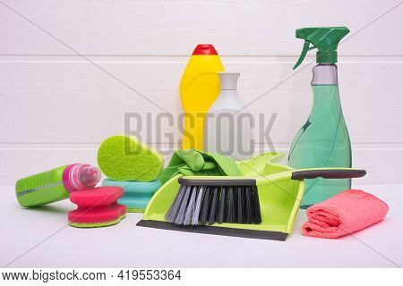 Green Scoop With A Duster, Colored Liquid For Cleaning The House, Colored Brushes And Rags On A Whit