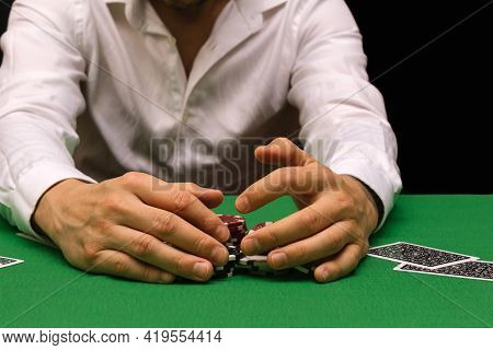 Man In A White Shirt Plays Poker In A Gambling Business In A Casino. Nightclub Industry. A Lot Of Mo