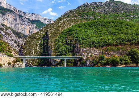 The bridge connects the banks of the canyon. Beautiful French Alps. The most beautiful and picturesque canyon in Europe - Verdon. The walls of the gorge are overgrown with bushes.