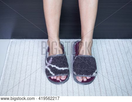 Slim Legs Woman In Slipper On Brown Doormat With Wooden Bed Background. Accessories Personal Use In