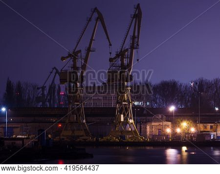 Szczecin, West Pomeranian - Poland - 2020: Shipyard Cranes And Quays At Night
