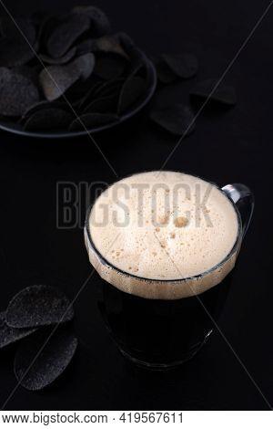 Dark Craft Beer With Black Potato Chips