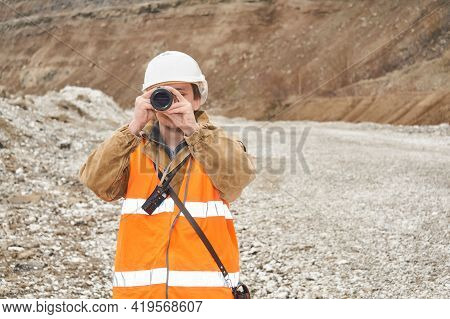 Mining Or Road Engineer Using A Spotting Scope Against The Background Of A Mine