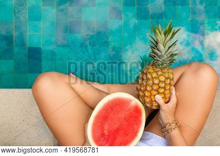 Women's Legs By The Pool With Tropical Fruits. Summer Concept.