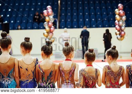 Gymnast Girls Stand Back To Back In A Row. The Award Ceremony After The Sports Competition. Female G