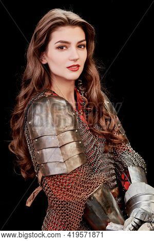 A beautiful noble warrior woman in chainmail and plate armor poses  on a black background. Medieval knight. Studio portrait.
