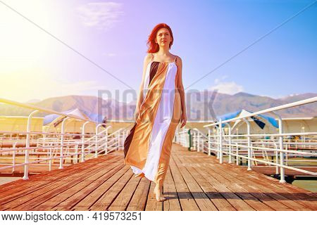 Red-haired Girl Posing In A Fluttering Dress. Woman On The Pier. Marine Wooden Pier With Umbrellas.