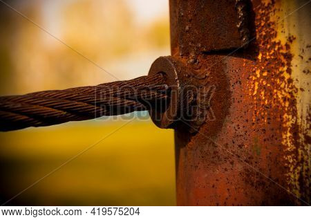 A close up image of a wire boundary rope welded to a metal pole to create a safety boundary in a wooded area.