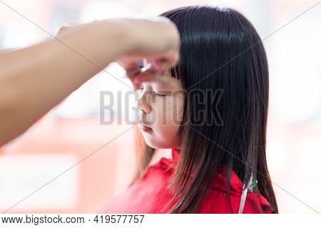 Cute Girl Cut The Bangs. The Barber's Hand Held Scissors Skillfully Cutting The Cutie Kid. Child Is