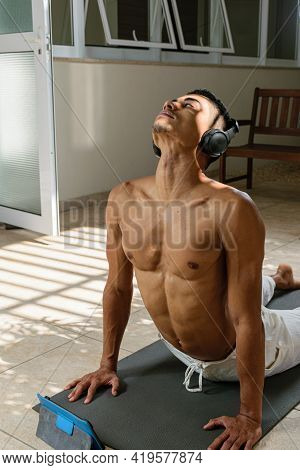 Young Brazilian Man Doing Online Yoga Class With Head Phone, In The Upward Facing Dog Position, Fron
