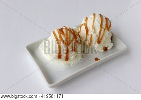 Vanilla Ice Cream Scoops With Caramel Topping On Plate On White Table Background. Frozen Yogurt With