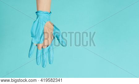 Close Up Of Hand Wearing Torn Medical Gloves Or Torn Rubber Gloves On Mint Green  Or Tiffany Blue Co