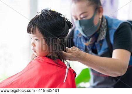 Bangkok Thailand - March 4, 2021; Cute Girl 4 Year Old Sitting Haircut By Professional Barber. Blur