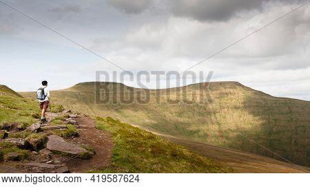 Asian Indian Woman Hiking Alone In Welsh Hills, Looking Towards Pen Y Fan, Brecon Beacons, Wales, Uk