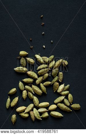 Close Up Photo Of Cardamom Pods And Seeds Pile On The Matt Black Background. It Is Very Popular In I