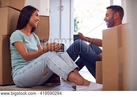 Couple Taking A Break Sitting On Floor Of New Home With Hot Drinks On Moving Day