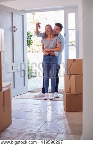 Excited Couple With Keys To New Home Standing By Front Door On Moving Day