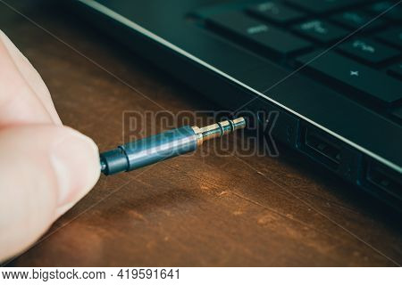 Hand Inserts Headphone Cable In Headphone Jack Of A Notebook