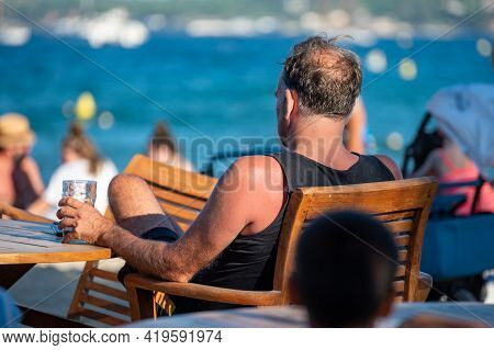 Unidentified Man Sitting In Beach Cafe With Glass Of Drink En Looking To Blue Water Of Gulf Of Saint