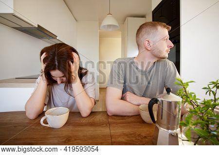Love, Quarrel, Stress And Relationship Concept - Portrait Of Sad Couple Sitting In Modern Kitchen Af