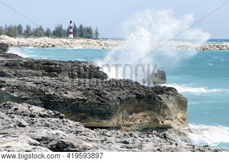 The View Of A Wave Hitting The Eroded Grand Bahama Island Coastline And A Lighthouse In A Background
