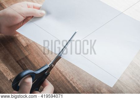 Pair Of Scissors Cutting White Paper, Holded By Male Hands