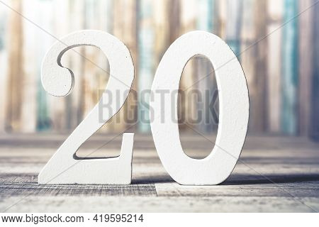 Number 20 Standing On A Gray Wooden Board