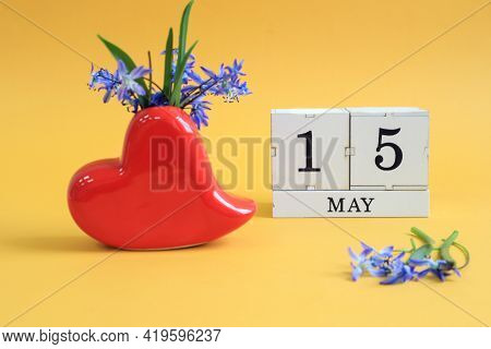 Calendar For May 15 : A Bouquet In A Heart-shaped Vase With Blue Flowers And The Numbers 15 On Cubes