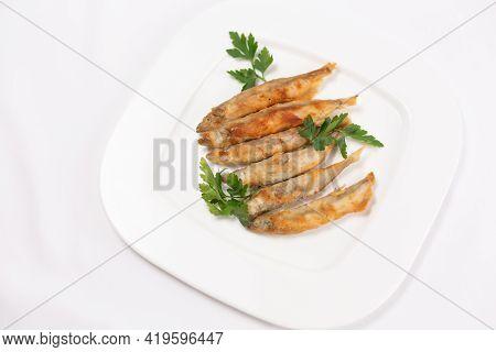 Fried Crispy Capelin On A White Plate