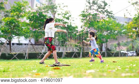 Mother And Daughter Were Playing In The Lawn. Families Play Fights With Fun. Asian Cute Girl Ran And
