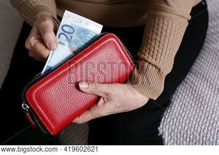 Elderly Woman Takes Out A Euro Note From Her Wallet. Concept Of Pension Payments, Savings At Retirem