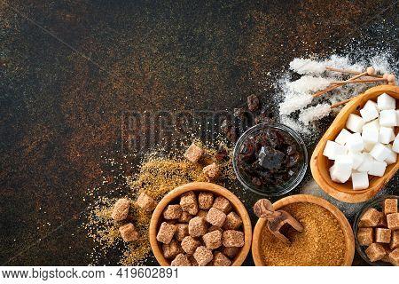 White Sugar, Cane Sugar Cubes, Caramel In Bamboo Bowl On Dark Brown Table Concrete Background. Assor