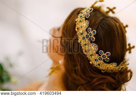 A Woman With A Beautiful Hairstyle In A Gold Crown With Stones, Close-up. Bride Wearing A Crown On A