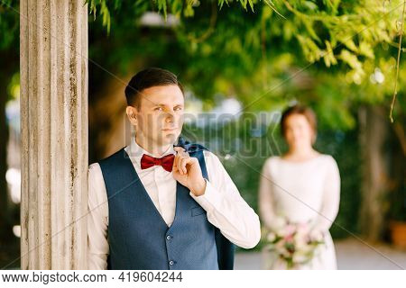 Smiling Groom Threw His Jacket Over His Shoulder. Groom Leaned Against A Column In The Garden