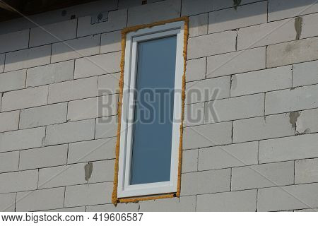 One White Rectangular Window On A Gray Brick Wall Of A House On The Street