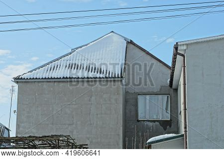 Window On A Gray Concrete Wall Of An Attic Of A Private House Under A Slate Roof In White Snow Again