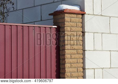 Part Of A Fence Made Of Red Metal And Brown Bricks Near The White Wall Of The House On The Street