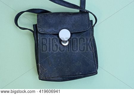 One Black Old Dirty Closed Leather Bag Lies On A Green Table
